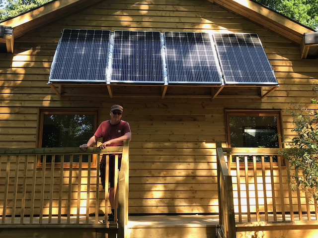 Photo showing a the Hideaway, a timber accommodation block at Hazel Hill Wood. It is powered by photovoltaics, which in this photo are seen fixed above the veranda